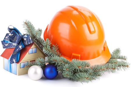 christmas savings: Hard hat, fir-tree branches, Christmas toys and small house on a white background.