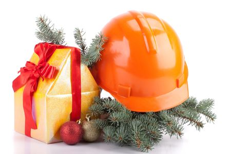 Hard hat, fir-tree branches, Christmas toys and small house on a white background. photo