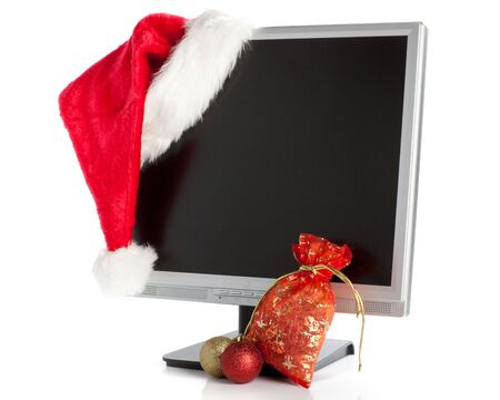 Modern flat screen LCD monitor in Christmas red hat on a white background. photo