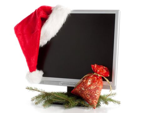 Modern flat screen LCD monitor in Christmas red hat with branch of fir-tree on a white background. photo