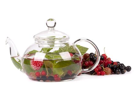Teapot with fruit tea and green leaves over white background photo