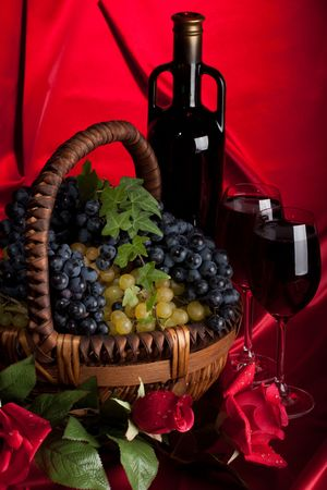 Appetizing grapes in a basket and bottle of wine on a red background. photo