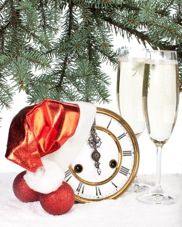 Two glasses of champagne and clocks in a Christmas cap on snow photo