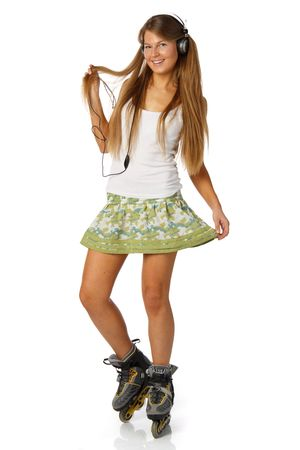 The beautiful girl with earphones in rollerskates on a white background. photo