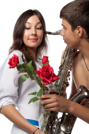 The male  patient gives a flower to the beautiful female doctor with a saxophone on a white background. photo