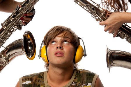 loud noise: The young man in ear-phones and two saxophones. Loud noise. Stock Photo