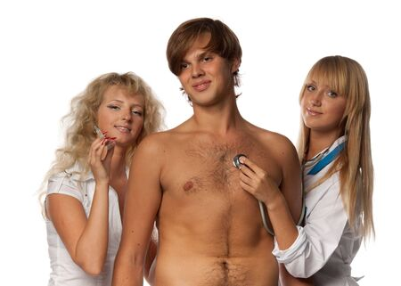 sexy female doctor: Two sexual nurses and the young male patient on a white background.