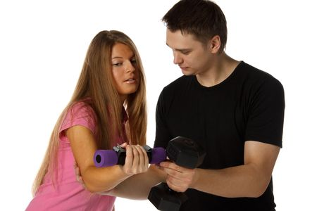 The young man and the girl with dumbbells on a white background. The trainer. photo