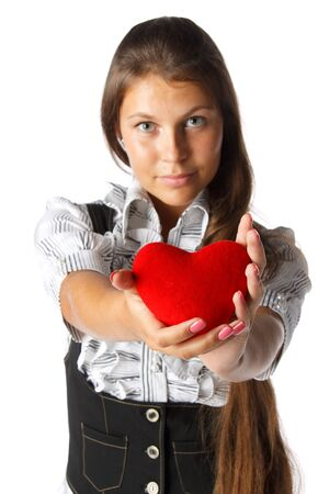 The beautiful girl holds in hands a red heart on a white background. photo