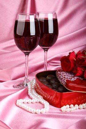 Heart-shaped red box with sweets, two glasses of red wine  and bunch of flowers. Valentines day card. photo