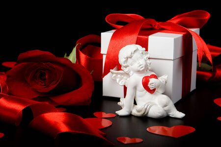 Gift box, cupid, red hearts and rose on a black background. Valentines day card. photo
