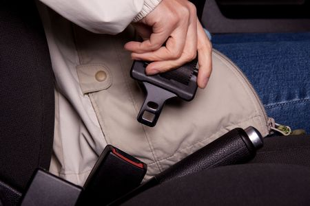 safe driving: Female hand  fastening  a seat belt in the car.