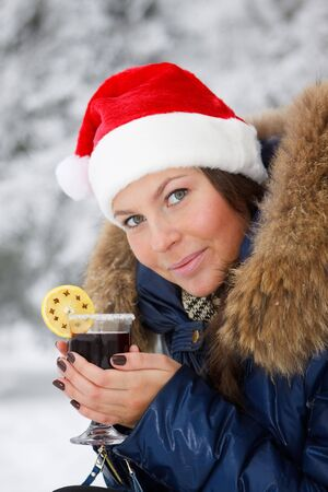 The beautiful girl in Santas cap drinks mulled wine in winter wood. photo