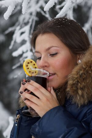 The beautiful girl drinks mulled wine in winter wood. Stock Photo - 6358907