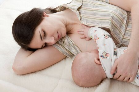 Young mum nurses the child on a white background