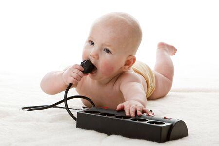 danger: Dolce piccolo bambino con spina elettrica su uno sfondo bianco.