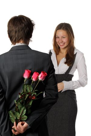 The young enamoured man with flowers and his girlfriend on a white background. Selective focus on flowers. Stock Photo - 6381832