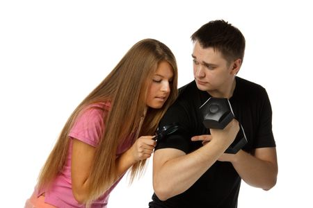 The beautiful girl considers a biceps of the young man by means of a magnifier. photo