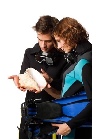 Young happy people with diving suits with a seashell on a white background. photo