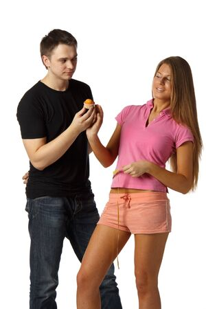 The young man offers delicious cake to the girl on a white background. Healthy food concept. photo
