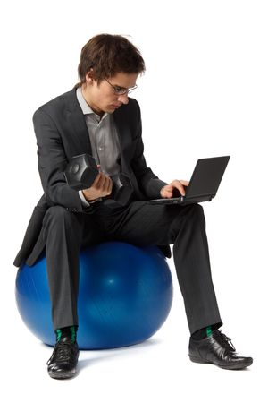 simultaneously: The young businessman simultaneously works on the computer and and does exercise with dumbbells.