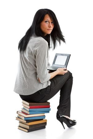 The attractive student sits on a pile of books with the laptop on a white background. photo