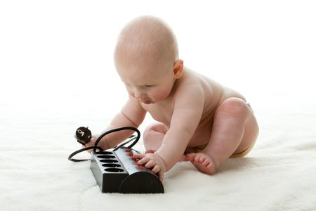 Sweet small baby with electric plug on a white background. photo