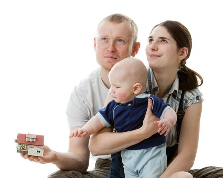 Father with  house  model, mother and  their sweet  baby on a white background. �oncept of purchase of the house. photo