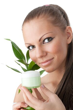 The attractive girl with a branch of a bamboo and a cosmetics jar on a white background Stock Photo - 6427688