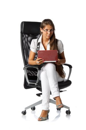 The attractive young woman with the laptop sits in an armchair on a white background. photo