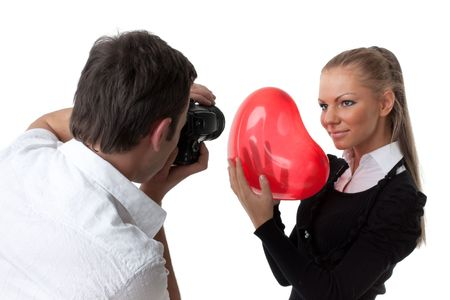 The beautiful girl with a red heart poses for the young guy on a white background. Selective focus on photographer. photo