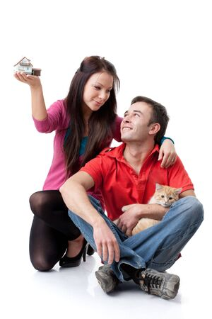 The young happy family with kitten holds house model in hands on a white background. House purchase concept. Stock Photo - 6476984