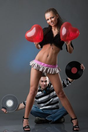 Male DJ and beautiful girl with vinyl disks on a grey background Stock Photo - 6476954