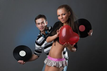 Male DJ and beautiful girl with vinyl disks on a grey background Stock Photo - 6476950