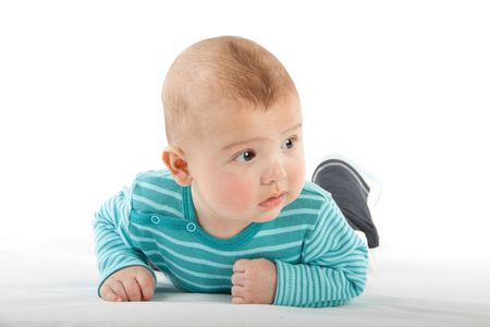 The nice small child in striped rompers lays on a stomach on a white background. photo
