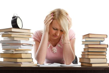 Stressed young woman  at a table among books on a white background photo