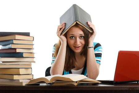 learning by doing: Stressed young woman sitting at a table among books and  laptop on a white background Stock Photo
