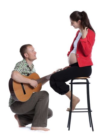 The young husband plays a guitar for the pregnant wife and the future child on a white background. photo