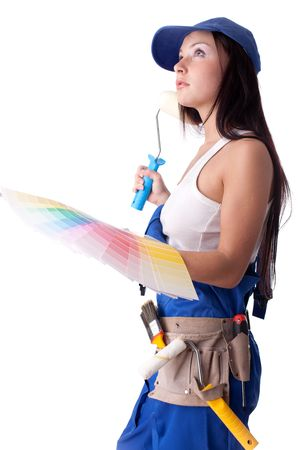 Young woman in overalls with a color guide and paintbrush on a white background. photo