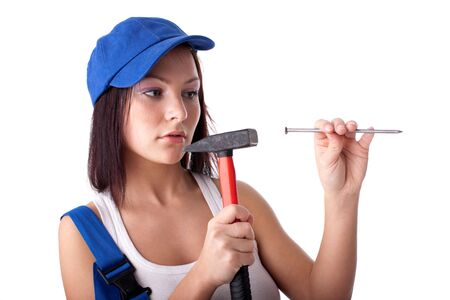 Young woman in overalls with hammer and nail on a white background. Stock Photo - 6594309