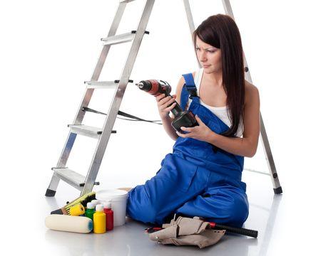 overol: La joven mujer en monos se sienta con diversas herramientas de construcci�n cerca de una escalera sobre un fondo blanco. Foto de archivo