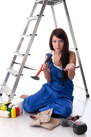 The young woman in overalls sits with various building tools near a step-ladder on a white background. photo