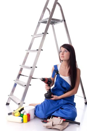 stepladder: The young woman in overalls sits with various building tools near a step-ladder on a white background.