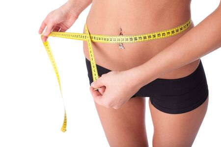 loss: The beautiful girl measures a waist on a white background.  Healthy lifestyles concept.