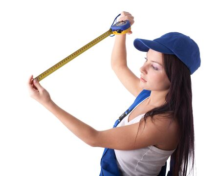 The beautiful young woman in overalls with a measuring tape in hands on a white background. photo