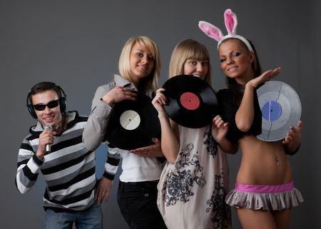 Male DJ and beautiful girls with vinyl disks on a grey background photo