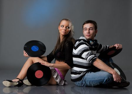 Male DJ and beautiful girl with vinyl disks on a grey background photo