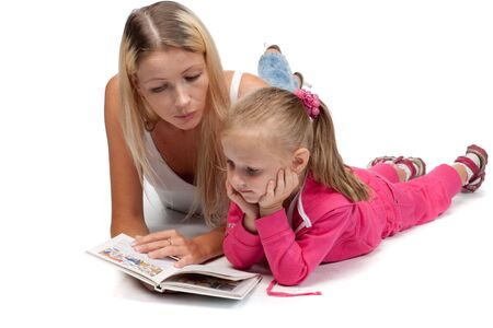 Young mum reads the interesting book to the daughter on a white background. Stock Photo - 6661944