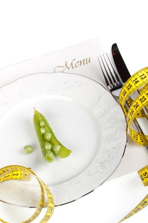 starvation: Pea and measure tape on a plate over white background Stock Photo