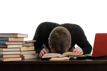 examination stress: Stressed young man sitting at a table among books and  laptop on a white background